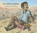 """""""Two White Rabbits"""" by Jairo Buitrago. Image: Father with brown skin, dark hair and a mustache, sitting in the desert looking over his shoulder. A child with brown hair in ponytails is resting her head on his legs, playing with a stuffed bunny."""
